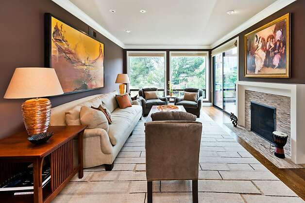 The large living room features hardwood flooring, recessed lighting, walls of windows and a fireplace. Photo: Olga Soboleva