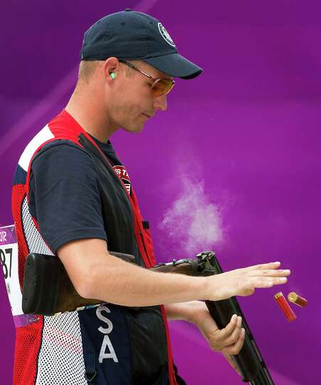 Glenn Eller ejects shells from his gun as he competes in the men's double trap qualification at the