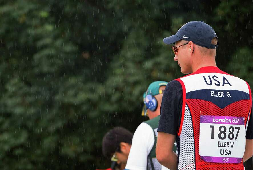 Glenn Eller waits to shoot in as a light rain falls while he competes in the men's double trap quali