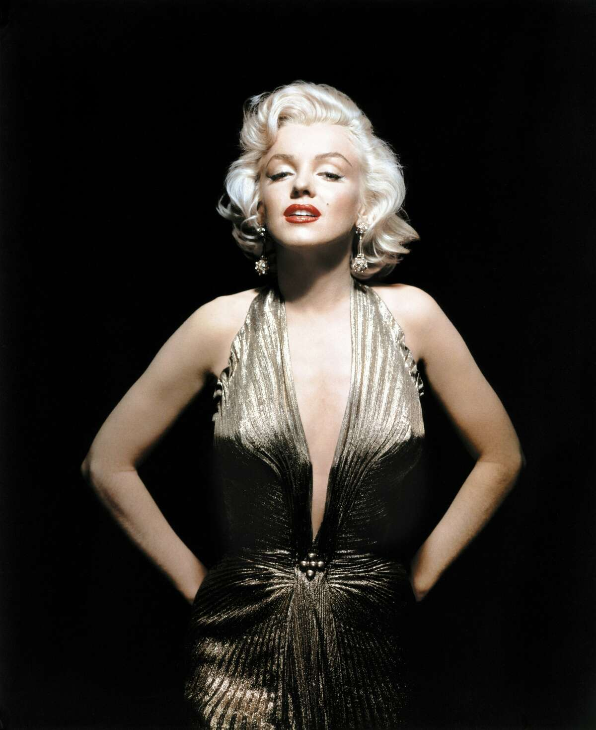 Marilyn Monroe is sultry in William Travilla's gold lame knife-pleated gown with a halter neckline and style lines that are somewhat Egyptian. She wore it for a scene in