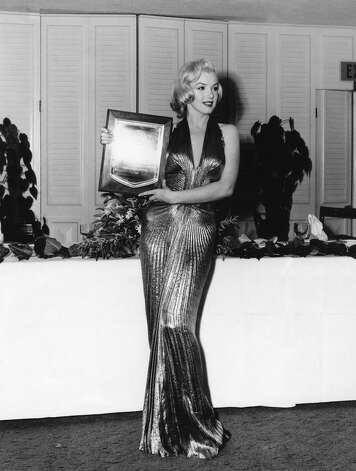 "In this March 1953 publicity photo provided by Running Press, Marilyn Monroe receives an award from Photoplay magazine at the Beverly Hills Hotel, in Beverly Hills, Calif. She is named ""Fastest Rising Star of 1952,"" and her choice of attire overshadows the event. The entire gown was made from ""one complete circle of fabric."" (AP Photo/Courtesy Running Press) (Associated Press)"