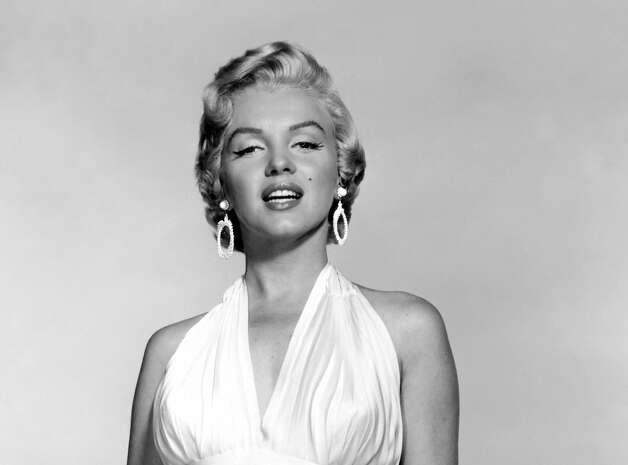 """In this undated publicity photo courtesy Running Press, Marilyn Monroe is shown in the first photo taken of her in the famous white dress from the """"The Seven Year Itch."""" For a brief scene in """"The Seven Year Itch,"""" in September 1954, her character strolls on a Manhattan street on a stifling summer evening. When a subway rattles beneath her, Marilyn stands astride a sidewalk vent to catch a cool breeze that swirls her skirt up around"""