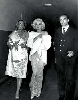 Marilyn Monroe walks with friends on the evening that she sang Happy Birthday to President John F. Kennedy on his 45th birthday. She wears a form-fitting gown designed by Jean Louis, head designer for Columbia Pictures at the time. The see-through flesh-hued gown, sans undergarments, is embroidered with rhinestones. But she did accessorize with with earrings, a fur wrap and heels. (Reprinted with permission from t)
