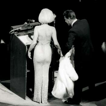"""In this May 19, 1962 publicity photo provided by Running Press, Peter Lawford, right, tends to Marilyn Monroe's fur as she prepares to sing """"Happy Birthday"""" to President John F. Kennedy at a Madison Square Garden gala in New York. (AP Photo/Courtesy Running Press) (Associated Press)"""