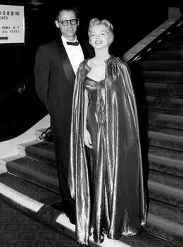 """In this late October 1956 publicity photo provided by Running Press, Marilyn Monroe, right, with husband Arthur Miller, is shown in the final weeks of filming """"The Prince and the Showgirl."""" This goddess-like ensemble is in a burnished gold lamé. (AP Photo/Courtesy Running Press) (Associated Press)"""