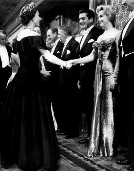 """In this late October 1956 photo provided by courtesy Running Press, Marilyn Monroe, right,  wearing a burnished gold lamé gown meets Queen Elizabeth in London. The photograph is included in a new 2012 book, """"Marilyn in Fashion,"""" published by Running Press. Monroe passed away a half-century ago this week, a murky death that remains one of Hollywood's most tantalizing mysteries. But look around: Her legend lives on, more vibrantly than ever. In a twist she surely would have appreciated, this 1950's bombshell has become a 21st-century pop culture phenom. (AP Photo/Courtesy Running Press) (Associated Press)"""