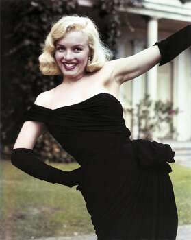 In 1950, Marilyn Monroe wears a black crepe cocktail dress by Ceil Chapman. Chapman's trademark is the gathering of fabric onto a hip, topped by a rosette. The opera-length gloves add sophistication to the single shoulder strapped dress. (Reprinted with permission from t)