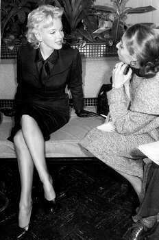 Marilyn Monroe, in a black wool suit in 1956 by designer George Nardiello. She's intervied by a reporter in a lounge at the Los Angeles International Airport. She wore the suit with a black satin shirt and matching necktie, leather glvoes and pumps. (Reprinted with permission from t)