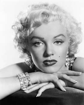 Before she was an actress, Marilyn Monroe was a model and learned how to do her own makeup that included an over-drawn upper lip and false eyelashes as show in this 1952 portrait. Later, makeup artists soon learned about Monroe's attention to such details (Reprinted with permission from t)