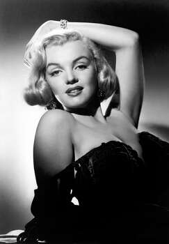 """Marilyn Monroe strikes a provocative pose in this Oleg Cassini basket weave chocolate velvet gown he had designed for wife Gene Tierney and that a fan magazine declared """"the most risque design of the year."""" Cassini, in 1961, was appointed by Jacqueline Kennedy as the official couturier for the first lady and created the """"Jackie Look"""" for her of stripped down versions of Chanel and pillbox hats. (Reprinted with permission from t)"""