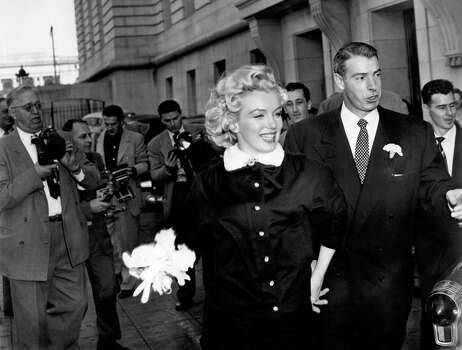 Mr. and Mrs. Joe DiMaggio emerge from their civil wedding ceremony in San Francisco on Jan. 14, 1954. Marilyn Monroe selected the Charles LeMaire buttoned up, three-quarter length suit with a white ermine collar for the ceremony. (Reprinted with permission from t)