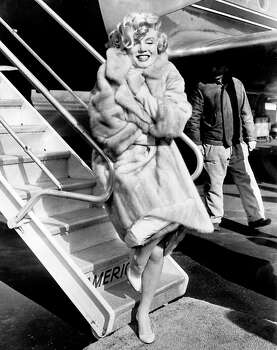 """(FILES)American actress Marilyn Monroe poses in 1959 for the photographers at La Guardia Airport before to fly to Chicago, for the presentation of her film """"Some like it hot"""". She was the prototype blonde bombshell and 50 years after her sudden death, the smoke from Marilyn Monroe's one-woman sexual revolution has yet to clear. Monroe wasn't the first Hollywood pin-up. Or even a natural blonde. But between the famous tight red sweater, the Playboy pictures, and that skirt blowing episode over a New York subway grate, the young woman previously known as Norma Jean Baker put America and the world in a fluster.  AFP PHOTO/FILESSTR/AFP/GettyImages (STR / AFP/Getty Images)"""