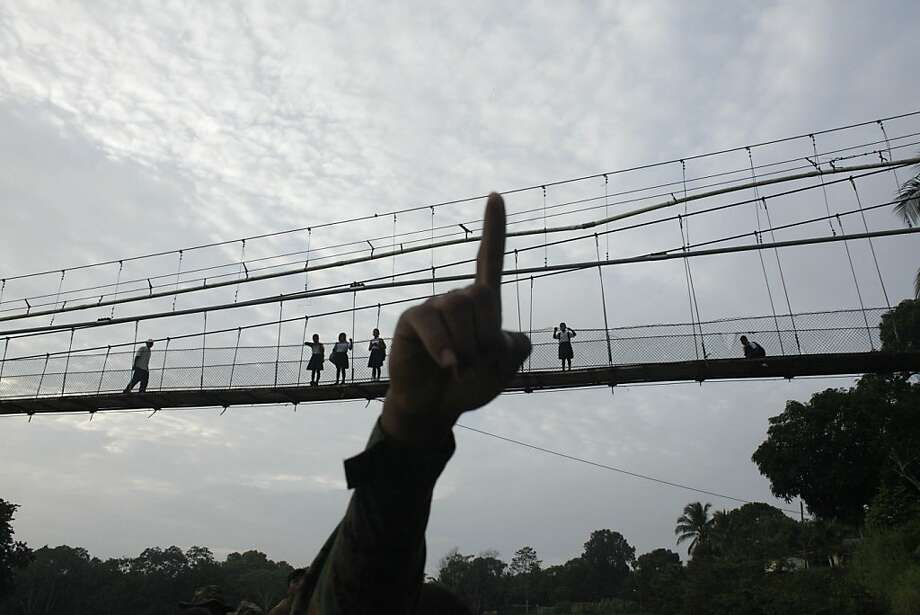 In this June 19, 2012 photo, a Panama border police officer points as he begins to patrol in the Darien province, on the border with Colombia, in Yaviza, Panama. Panamanian authorities began noticing five years ago that the Darien Gap, the only interruption in the Pan-American Highway, was being used by migrant smugglers, usually to move people from Asia and Africa. Panama's Public Safety Minister Jose Murillo says that the movement of people from Asia and Africa has tapered off but that hundreds of Cubans are now taking the arduous Darien Gap route toward the United States. (AP Photo/Arnulfo Franco) Photo: Arnulfo Franco, Associated Press