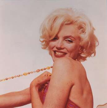 """This photograph released by the Brooklyn Museum of Art, titled """"Marilyn Monroe: Pulling Beads,"""" is part of show opening at the museum Friday, Nov. 12, 2004. The 1962 pink tinted photograph by Bert Stern is one of more than 200 Monroe pictures from 39 photographers - including luminaries such as Richard Avedon, Gordon Parks, Robert Frank and Andy Warhol - in the museum's new exhibit, """"I Want to Be Loved by You: Photographs of Marilyn Monroe."""" (AP Photo/Brooklyn Museum of Art, Bert Stern) (BERT STERN / AP)"""