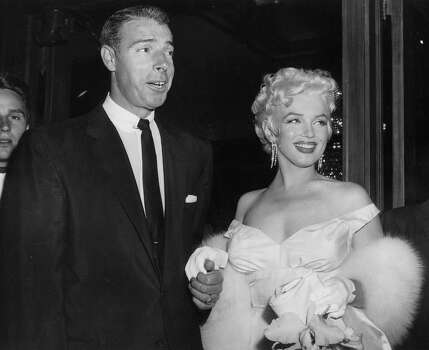 FILE - In this June 2, 1955 file photo, actress Marilyn Monroe, right, in a glamorous evening gown, with Joe DiMaggio, arrives at the theater. (AP Photo, File) (Associated Press)