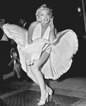 """FILE - In this Sept. 9, 1954 file photo, Marilyn Monroe poses over the updraft of New York subway grating while in character for the filming of """"The Seven Year Itch"""" in Manhattan. The former Norma Jean Baker modeled and starred in 28 movies grossing $200 million. Sensual and seductive, but with an air of innocence, Monroe became one of the world's most adored sex symbols. She died alone by suicide, at age 36 in her Hollywood bungalow.  (AP Photo/Matty Zimmerman, File) (Matty Zimmerman / Associated Press)"""
