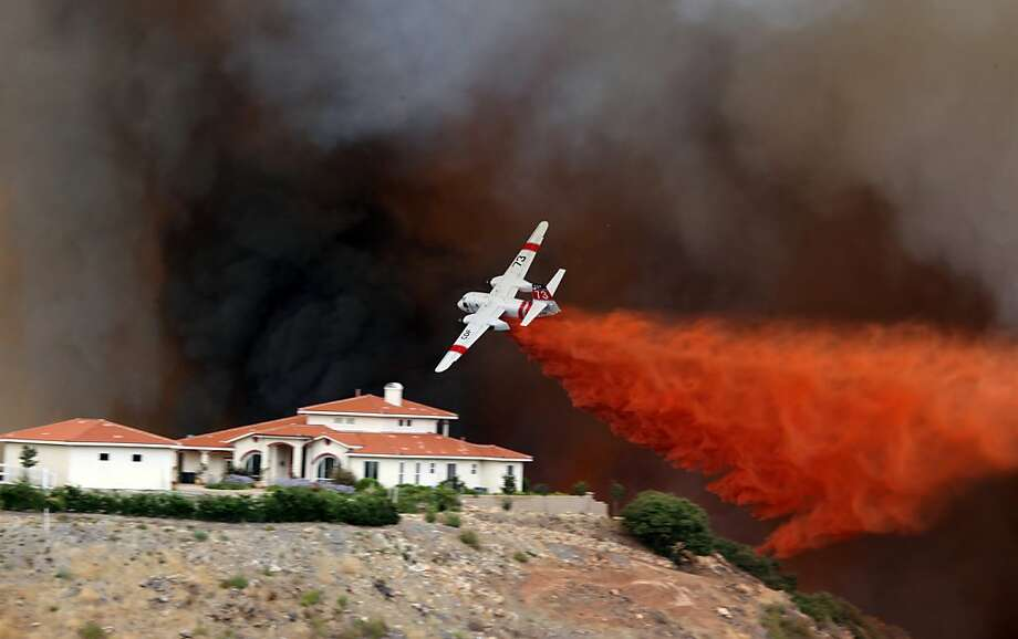 A firefighting air tanker drops fire retardant on a hillside as a wildfire rages, Wednesday Aug. 1, 2012 in Murrieta, Calif. Several homes were threatened by the wildfire that burned more than 200 acres. (AP Photo/Mike Shelhart) Photo: Mike Shelhart, Associated Press