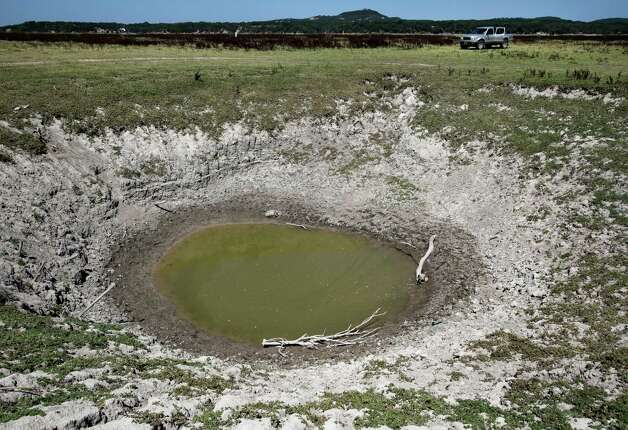 A giant sink hole in Medina Lake is seen in Thursday Aug. 2, 2012 on the dry lake bed in front of the Holiday Villages community. The Texas Water Development Board's website reports the lake is 59.59 feet low and is currently only 16.09 percent full. Holiday Villages sales representative C.R. Edwards says the sink hole is called Jacobs Well by locals and is thought to connect to the aquifer. Photo: William Luther, San Antonio Express-News / © 2012 San Antonio Express-News
