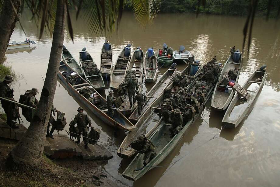 In this June 19, 2012 photo, Panama border police load boats with equipment and supplies to begin patrolling in the Darien province on the border with Colombia, in Yaviza, Panama. Panamanian authorities began noticing five years ago that the Darien Gap, the only interruption in the Pan-American Highway, was being used by migrant smugglers, usually to move people from Asia and Africa. Panama's Public Safety Minister Jose Murillo says that the movement of people from Asia and Africa has tapered off but that hundreds of Cubans are now taking the arduous Darien Gap route toward the United States. (AP Photo/Arnulfo Franco) Photo: Arnulfo Franco, Associated Press