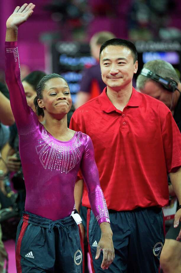 A relieved U.S. gymnast Gabrielle Douglas waves to the crowd with her coach Liang Chow after performing on the floor exercise during the women's gymnastics individual all-around final. ( Smiley N. Pool / Houston Chronicle ) Photo: Smiley N. Pool, Houston Chronicle / © 2012  Houston Chronicle