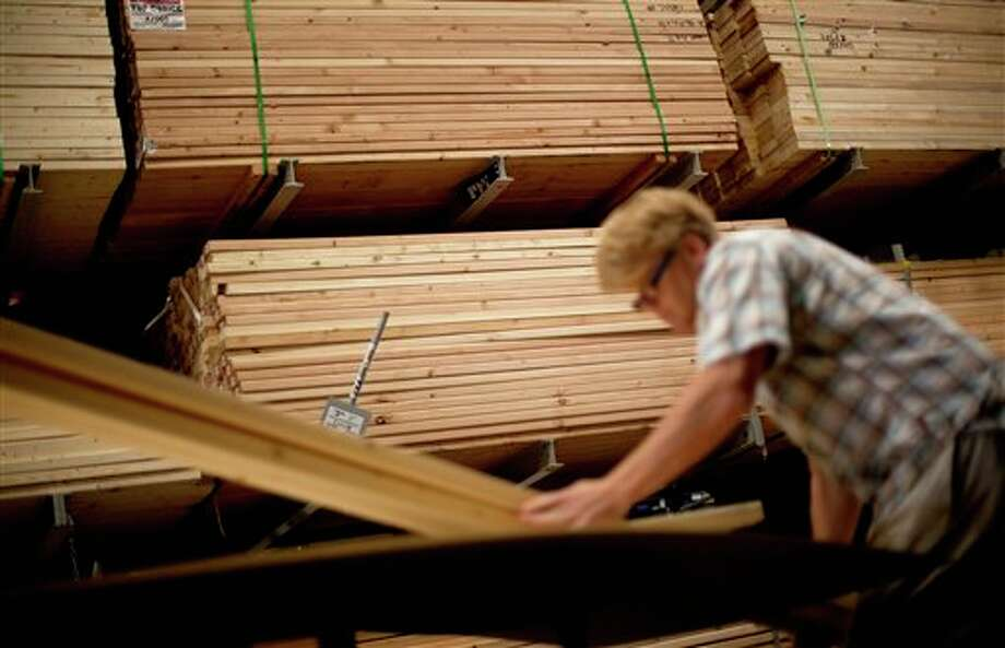 In this Tuesday, June 19, 2012, photo, Michael McGehee, of Atlanta, loads lumber onto a cart while shopping at Lowe's store in Atlanta.  The government reports on the number of orders businesses placed to U.S. factories in June. Forecast is that orders rose 0.3 percent after having risen 0.9 percent in May. A preliminary report showed a surge in volatile aircraft orders drove demand for long-lasting manufactured goods higher in June. (AP Photo/David Goldman) Photo: David Goldman, AP / AP