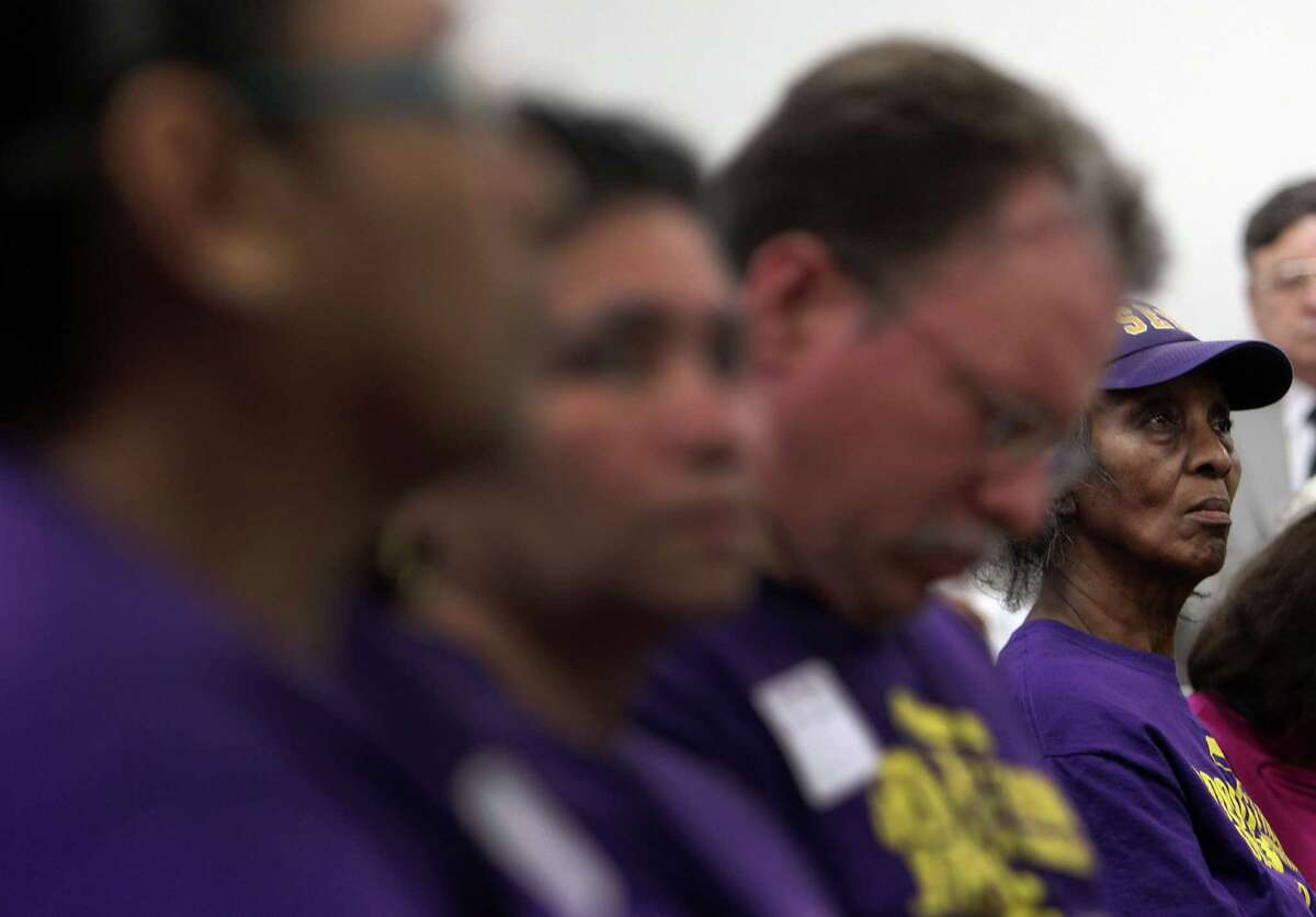 SEIU member Alice McAfee listens during a news conference at which clergy of multiple faiths expressed their support for janitors but encouraged them not to try to be arrested during demonstrations.