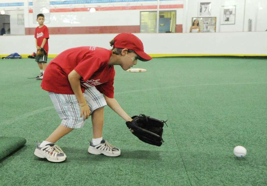 Joseph Mollica, 9, of the Angels, fields a ball during the Greenwich Parks and Recreation Department's Summer Baseball All-Star Challenge at Hamill Rink and the Byram Baseball Field, Thursday night, Aug. 2, 2012. Photo: Bob Luckey / Greenwich Time