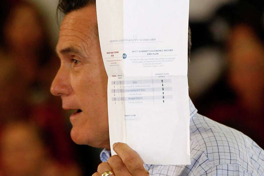"""Republican presidential candidate, former Massachusetts Gov. Mitt Romney holds up a """"presidential accountability scorecard"""" comparing himself to President Barack Obama, as he campaigns at the Jefferson County Fairgrounds in Golden, Colo., Thursday, Aug. 2, 2012. (AP Photo/Charles Dharapak) Photo: Charles Dharapak / AP"""