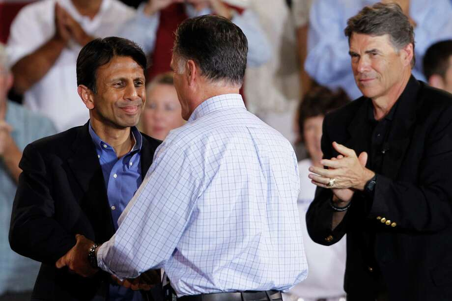 GOP presidential candidate Mitt Romney greets Louisiana Gov. Bobby Jindal with Texas Gov. Rick Perry, right, in August at a campaign rally in Basalt, Colo. Perry was on his way to Aspen for a Republican Governors Association event. Photo: Charles Dharapak / AP