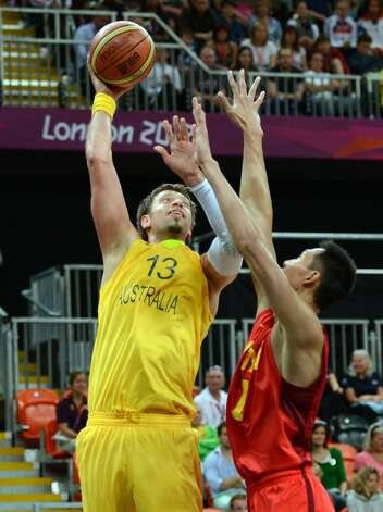Australian forward David Andersen (L) vies with Chinese centre Yi Jianlian during the men's preliminary round basketball match Australia vs China of the London 2012 Olympic Games on August 2, 2012 at the basketball arena in London. (TIMOTHY A. CLARY / AFP/Getty Images)