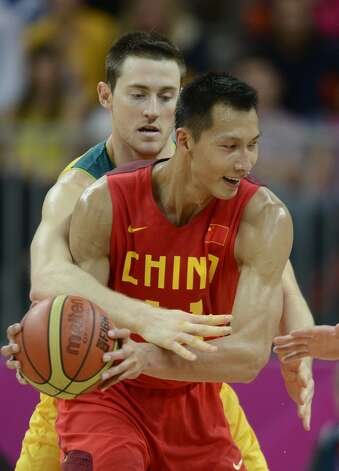 Chinese centre Yi Jianlian vies with Australian centre Aron Baynes during the men's preliminary round Groupe B basketball match Australia vs China of the London 2012 Olympic Games  on August 2, 2012 at the basketball arena in London. (TIMOTHY A. CLARY / AFP/Getty Images)