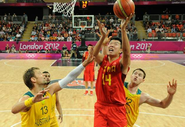 Chinese guard Wang Zhizhi (C) jumps to score against Australian forward David Andersen (L) and Australian centre Aron Baynes (R) during the men's preliminary round Groupe B basketball match Australia vs China of the London 2012 Olympic Games  on August 2, 2012 at the basketball arena in London. (MARK RALSTON / AFP/Getty Images)