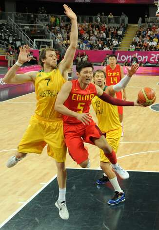 Chinese guard Liu Wei (C) vies with Australian forward Joe Ingles (L) during the men's preliminary round Groupe B basketball match Australia vs China of the London 2012 Olympic Games  on August 2, 2012 at the basketball arena in London. (MARK RALSTON / AFP/Getty Images)