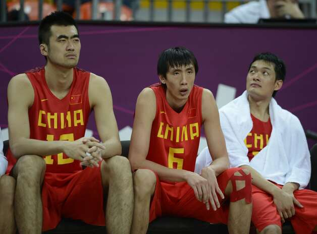 Chinese centre Zhang Zhaoxu (L) and Chinese forward Yi Li (C) sit on a bench during the men's preliminary round Groupe B basketball match Australia vs China of the London 2012 Olympic Games  on August 2, 2012 at the basketball arena in London. (TIMOTHY A. CLARY / AFP/Getty Images)