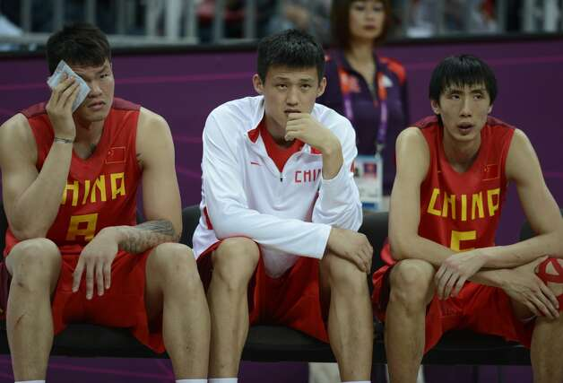 Chinese forward Zhu Fangyu (L), Chinese forward Zhou Peng and Chinese forward Yi Li (R) sit on a bench during the men's preliminary round Groupe B basketball match Australia vs China of the London 2012 Olympic Games  on August 2, 2012 at the basketball arena in London. (TIMOTHY A. CLARY / AFP/Getty Images)