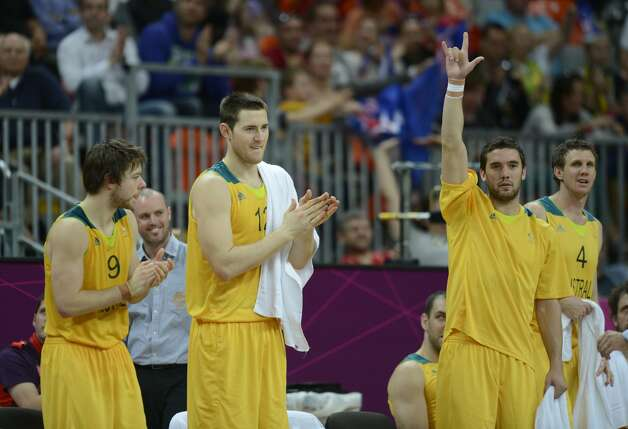 Australian guard Matt Dellavedova (L), Australian centre Aron Baynes and Australian guard Adam Gibson (R) celebrate at the end of the men's preliminary round Groupe B basketball match Australia vs China of the London 2012 Olympic Games  on August 2, 2012 at the basketball arena in London. Australia won 49-23. (TIMOTHY A. CLARY / AFP/Getty Images)