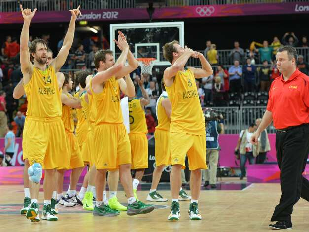 Australian players celebrate next to Chinese coach Robert Donewald Jr at the end of the men's preliminary round Groupe B basketball match Australia vs China of the London 2012 Olympic Games  on August 2, 2012 at the basketball arena in London. Australia won 49-23. (MARK RALSTON / AFP/Getty Images)