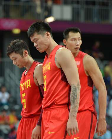 Chinese guard Liu Wei (L) and Chinese forward Zhu Fangyu (C) look dejected at the end of the men's preliminary round Groupe B basketball match Australia vs China of the London 2012 Olympic Games  on August 2, 2012 at the basketball arena in London. Australia won 49-23. (MARK RALSTON / AFP/Getty Images)