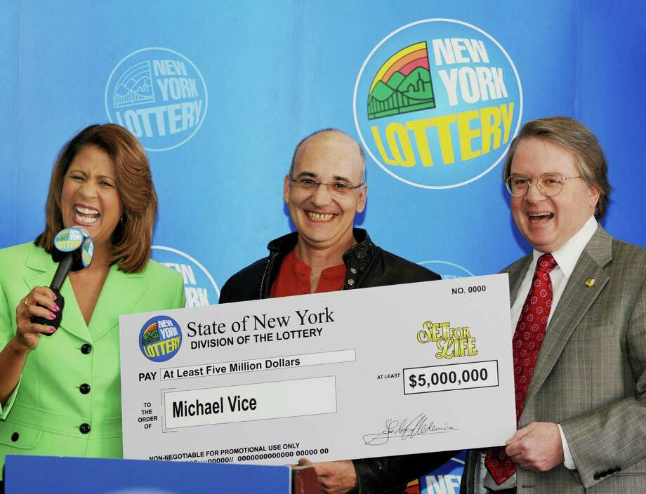 "Michael Vice, of Ticonderoga, center, smiles and holds the supersized check as he meets with the media with lottery spokesperson Yolanda Vega, left, and the Director of the New York Lottery, Gordon Medenica, right, on Tuesday, March 9, 2010, at New York Lottery Headquarters in Schenectady, NY.  The lottery held the press conference to present Vice, who won the ""Set for Life"" instant game at C&G Petroleum In his hometown of Ticonderoga that guarantees him a minimum of a $5,000,000 jackpot.  Vice will receive 20 annual payments to total the $5 million, and if he lives past the 20 years he will net a check of $171,678 for each additional year he survives.  The 46 year old is the first in Essex County to win a Lottery Jackpot in 2010.   (Luanne M. Ferris / Times Union) Photo: LUANNE M. FERRIS / 00007815A"