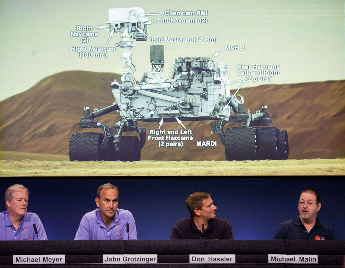 Scientists talks about the cameras aboard the Curiosity Mars Rover, background, during a media briefing at NASA's Jet Propulsion Laboratory in Pasadena, Calif., last week.