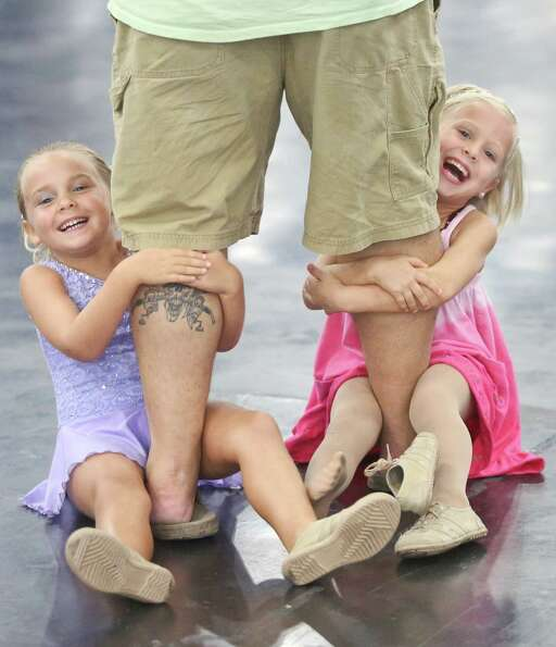 Emma Teas, left, 6 and Abby Gerlach, right, 6 hold on to Dan Gerlach's leg's  from Corpus Christi, w