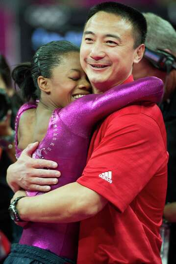 U.S. gymnast Gabrielle Douglas hugs her coach Liang Chow after performing on the floor exercise duri