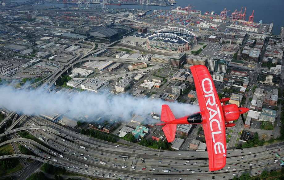 Sean D. Tucker lets some smoke fly from the Oracle Challenger III as he passes by the SODO area in Seattle. Photo: LINDSEY WASSON / SEATTLEPI.COM