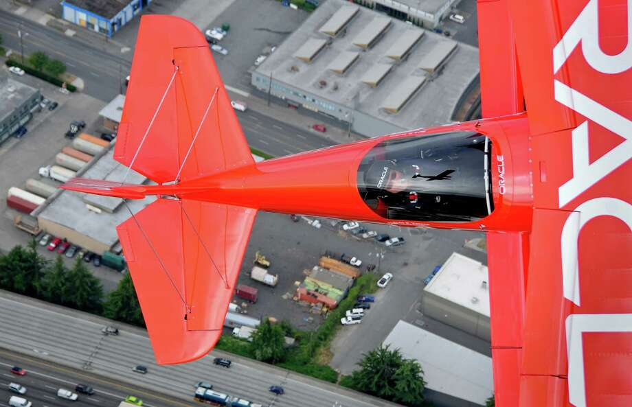 Sean D. Tucker smiles as he looks at the chase plane, reflected in the windshield, while flying the Oracle Challenger III on its side in Seattle on Thursday, August 2, 2012. Tucker, internatonally recognized as one of the premier civilian aerobatic performers worldwide, has logged over 24,000 flight hours and has been performing since the 1970s. Photo: LINDSEY WASSON / SEATTLEPI.COM