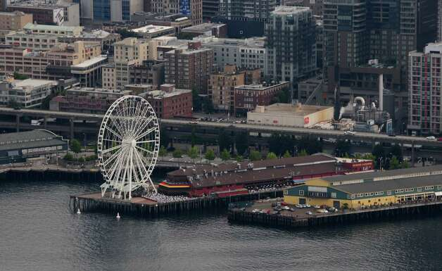 Seattle's Great Wheel stands out on the pier in downtown as seen from the Oracle chase plane on Thursday, August 2, 2012. Tucker, internatonally recognized as one of the premier civilian aerobatic performers worldwide, has logged over 24,000 flight hours and has been performing since the 1970s. Photo: LINDSEY WASSON / SEATTLEPI.COM