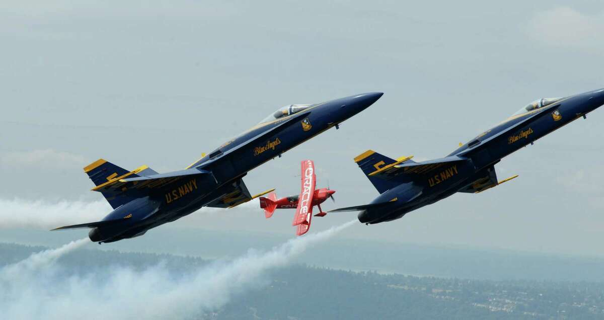 Team Oracle stunt pilot Sean D. Tucker flies in formation with U.S. Navy Blue Angels pilots Lt. C.J. Simonsen, left, and Lt. David Tickle, right, Thursday, Aug. 2, 2012, over Lake Washington, in Seattle.