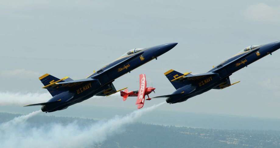 Team Oracle stunt pilot Sean D. Tucker flies in formation with U.S. Navy Blue Angels pilots Lt. C.J. Simonsen, left, and Lt. David Tickle, right, Thursday, Aug. 2, 2012, over Lake Washington, in Seattle. Photo: Ted S. Warren / Associated Press