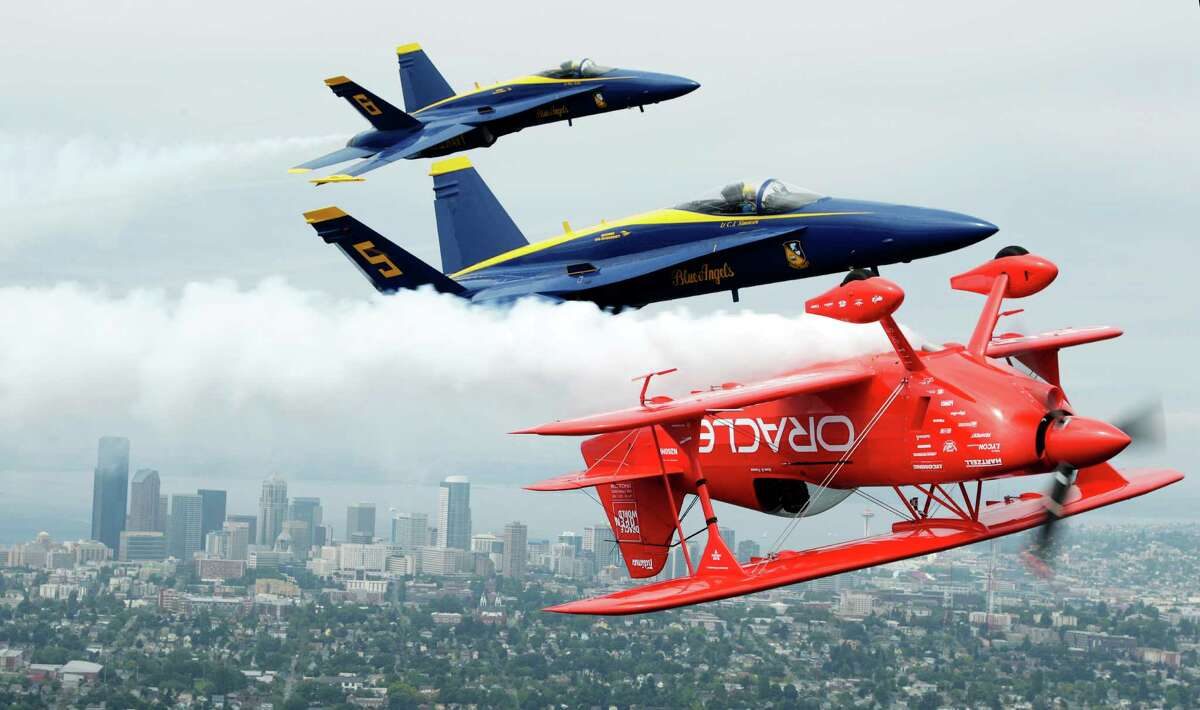 U.S. Navy Blue Angels pilots Lt. C.J. Simonsen (5) and Lt. David Tickle (6) fly in formation with Team Oracle stunt pilot Sean D. Tucker, Thursday, Aug. 2, 2012, near downtown Seattle.