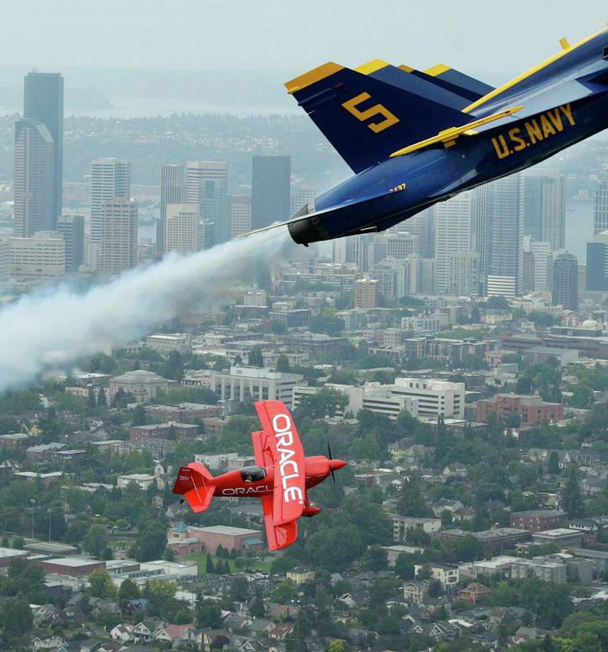 Team Oracle stunt pilot Sean D. Tucker flies in formation with two U.S. Navy Blue Angels, Thursday, Aug. 2, 2012, near downtown Seattle. Tucker and the Blue Angels are in town for the annual Seafair summer festival, which will feature an air show and other events this coming weekend. Photo: Ted S. Warren / Associated Press