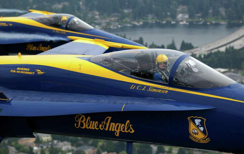 U.S. Navy Blue Angels pilots Lt. C.J. Simonsen, right, and Lt. David Tickle, upper left, fly in form